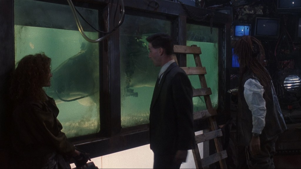 Still from Johnny Mnemonic, with Jane, Johnny, and J-Bone in front of the tank of Jones, the heroin addicted cybernetically augmented hacker Dolphin.